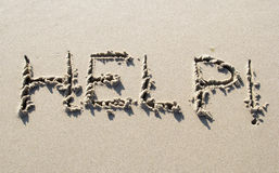 Help handwritten on sand beach. Help written on sand beach Royalty Free Stock Images