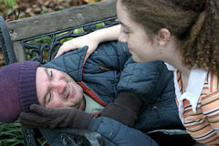 Help For Homeless Man. A homeless man being helped by a teen volunteer. (focus on homeless man's eyes stock images
