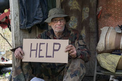 Help. Homeless man holds a paper cardboard sign that reads help Stock Photos