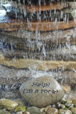 Help! I'm a rock. Whimsical fountain of stacked up rock with flowing water Stock Photo