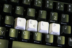 Help Keys Angled. Black computer keyboard with HELP written in white keys across the middle.  Shot at an angle Stock Images