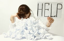 Help me. Despaired woman behind many crumpled paper holding help sign isolated on white background royalty free stock photo