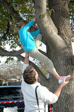 Help me Down. A little girl gets help from her grandpa as she climbs down out of a tree Stock Images