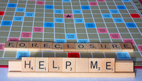 Help Me, Foreclosure. A cry for financial help spelled out on a board game stock photography