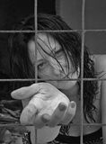 Help me please. The woman in jail - terrified views (behind bars) outstretched arms - hand , like a praying for help. Black and white vertical photo Royalty Free Stock Images