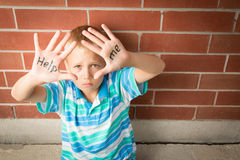 Help Me. A pre-teen boy is begging to help him showing the message written on his palms Royalty Free Stock Photos