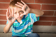 Help Me. A pre-teen boy is begging to help him showing the message written on his palms royalty free stock image
