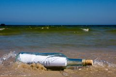Help message in bottle. In a sea shore Stock Photo