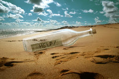 Help message in a bottle. On beach Royalty Free Stock Photo