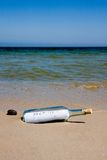 Help message in bottle. Close-up of help message in bottle on a sea shore Stock Image