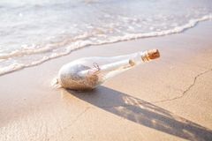Help message bottle beach. Message in a bottle on sand beach at sunset. Support and development stock photography