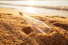Help message bottle beach. Message in a bottle on sand beach at sunset. Support and development Royalty Free Stock Photos