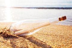 Help message bottle beach. Message in a bottle on sand beach at sunset. Support and development Royalty Free Stock Image