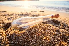 Help message bottle beach. Message in a bottle on sand beach at sunset. Support and development Stock Images