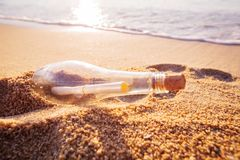 Help message bottle beach. Message in a bottle on sand beach at sunset. Support and development Stock Photo