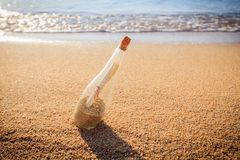 Help message bottle beach. Message in a bottle on sand beach at sunset. Support and development Stock Photos