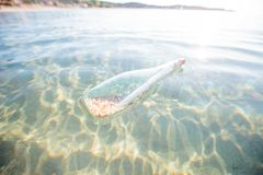 Help message bottle sea. Message in a bottle floating in the sea. Glass bottle with help message in the water Stock Images