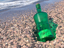 Help Message in a bottle on a shore concept. Background Royalty Free Stock Photos