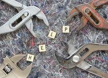 Help message Game tiles Aggresive adjustable pliers. Game tiles forming the word HELP surrounded by open mouthed pliers and wrench. Recycled painters drop cloth royalty free stock photo