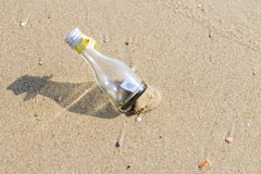 HELP message in glass bottle. On the beach Royalty Free Stock Photos