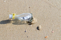 HELP message in glass bottle. On the beach Stock Photo