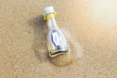 `HELP` message in glass bottle. On the beach Royalty Free Stock Photo