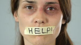 Help message on taped mouth of bruised woman, helpless silent abuse victim. Stock footage stock video