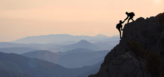 Help mountaineering & peak performance. Mountains and crazt position;help mountaineering & peak performance stock photo