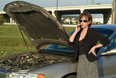 Help Needed. A woman with a cell phone and what appears to be car trouble royalty free stock images