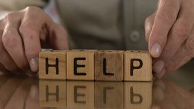 Help, old man making word of wooden cubes, support and assistance for elderly. Stock footage stock footage
