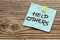 Help others reminder. Help others  reminder note against grained weathered wood Royalty Free Stock Images