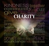 Help our Charity Fundraising campaign -. Male cupped hands emerging from black background surrounded by a warm colored CHARITY word cloud Royalty Free Stock Photos