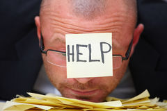 HELP -Overworked businessman Stock Photography