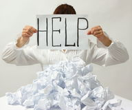 Help. Overworked woman behind many crumpled paper holding help sign isolated on white background stock photography