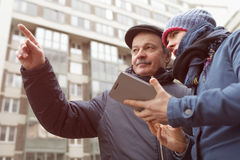 Help the passerby to find the right direction. A young girl with a tablet in her hands asks for directions from a stranger. He shows her  with finger the right Stock Photos