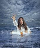 Businesswoman in the ocean with lifebelt asks help during a storm. Help request from a worker who is drowning in the sea royalty free stock photos