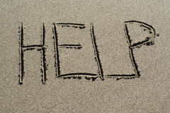Help in sand. Help spelled out on a beach Stock Photography