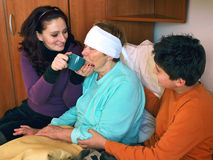 Help for sick grandmother. Daughter and grandson take care of sick grandmother  (bandaged head) in bed, give her a cup of hot drink because she has a fever Stock Photo