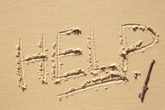 Help Sign on the beach. Help written in the sand on a beach Stock Photo