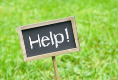 Help sign on a chalkboard stock image