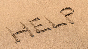 Help Sign Drawn On Sand. Help Sign Drawn On Beach Sand Royalty Free Stock Images