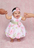 Help standing. Little hispanic girl standing with help from parents in pink floral outfit Royalty Free Stock Photo