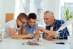 Positive joyful teacher helping his pupils royalty free stock image