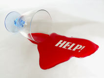 HELP text. Drinking glass with spilled red liquid spelling HELP text message Royalty Free Stock Photo