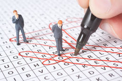 Help to find the job. Concept - words related to job in the word search game and helping (supervising) figures. Focused on word job Royalty Free Stock Photo