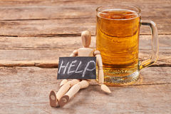 Help to get rid of alcohol. Human wooden figurine with message help, glass of beer, old wooden background Royalty Free Stock Photos