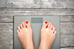 Help to lose kilograms with woman feet stepping on a weight scale Royalty Free Stock Images