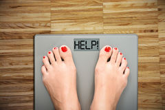 Help to lose kilograms with woman feet stepping on a weight scale. Woman stepping on a weight scale with the word 'help' on display stock photo