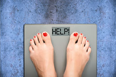 Help to lose kilograms with woman feet stepping on a weight scale. Woman feet stepping on a weight scale with the word 'help' written on display royalty free stock image