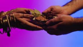 Help uw buren voorraad Een man deelt met een vrouw Indische kruiden als teken van vriendschap en medeleven stock footage